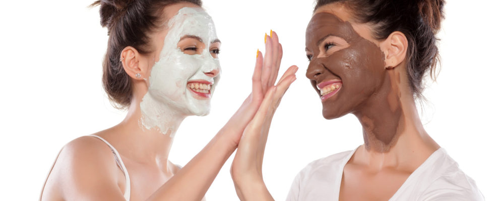 Two young women with masks making high five